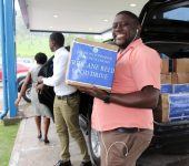 Division of Finance and the Economy Driver Davon Mc Kenna assisting with packing the boxes onto the vehicle at the Victor E. Bruce Financial Complex, prior to distribution.